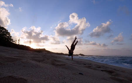 north shore: Man does one hand Handstand on beach at sunset as wave crash on the North Shore of Oahu, Hawaii.