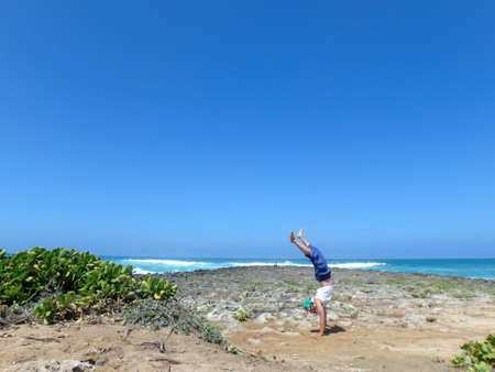 beach hunk: Man Handstanding on coral rocks on the beach as wave crash in the distance on the North Shore of Oahu, Hawaii.