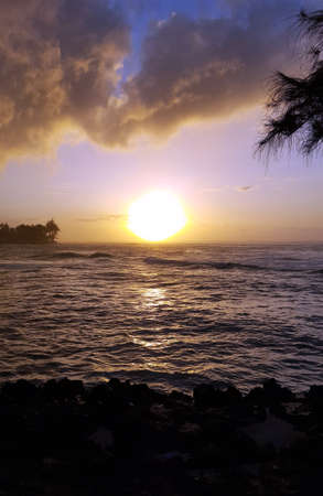 north shore: Beautiful Sunset over the ocean with waves moving to shore on the North Shore of Oahu.