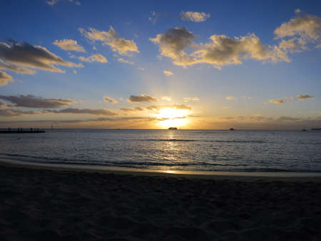 Dramatic Sunset dropping behind the ocean shining through boats on Waikiki Beach on Oahu, Hawaii. 版權商用圖片