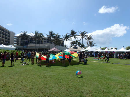 wanderlust: NORTH SHORE, HAWAII - FEBRUARY 27:  Group of  People throw balls in air with help of rainbow circle tarp outside at Wanderlust yoga event on the North Shore, Hawaii on February 27, 2016.