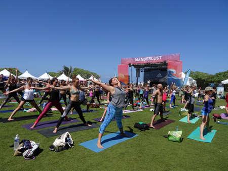 beine spreizen: NORTH SHORE, HAWAII - 28. Februar: Die Leute Arme weit anheben und gespreizten Beinen bei Outdoor-Yoga-Kurs bei Fernweh Yoga Event auf der North Shore, Hawaii am 28. Februar 2016 gegenüber der Bühne.