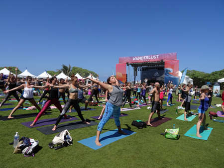 spread legs: NORTH SHORE, HAWAII - FEBRUARY 28: People raise arms wide and spread legs during outdoor yoga class facing stage at Wanderlust yoga event on the North Shore, Hawaii on February 28, 2016. Editorial