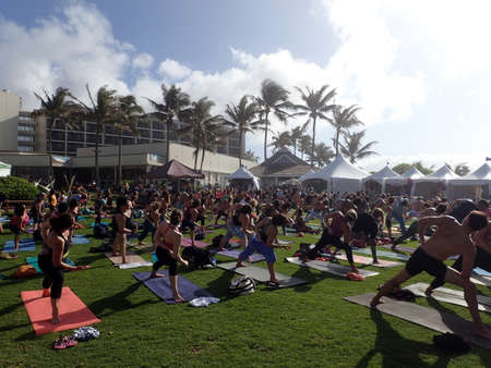 side angle pose: NORTH SHORE, HAWAII - FEBRUARY 25:  People do side angle pose, Utthita Parsvakonasana, at outdoor yoga class facing stage at Wanderlust yoga event on the North Shore, Hawaii on February 25, 2016. Editorial