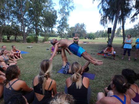 wanderlust: NORTH SHORE, HAWAII - FEBRUARY 26: AcroYoga Teacher Jason Nemer balances instructor as class watches demonstration at Wanderlust yoga event on the North Shore, Hawaii on February 26, 2016.