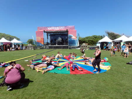 NORTH SHORE, HAWAII - FEBRUARY 27:  Group lays on rainbow tarp in Corpse pose at end of class outside at Wanderlust yoga event on the North Shore, Hawaii on February 27, 2016.