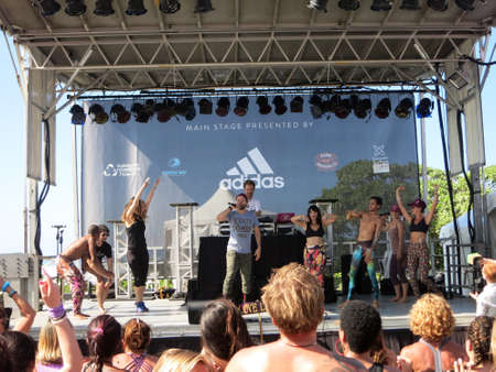 mc: NORTH SHORE, HAWAII - FEBRUARY 28:  Wanderlust Yoga Class dances to Music of MC Yogi preforming on stage with people dancing at outdoor yoga class facing stage at Wanderlust yoga event on the North Shore, Hawaii on February 28, 2016. Editorial