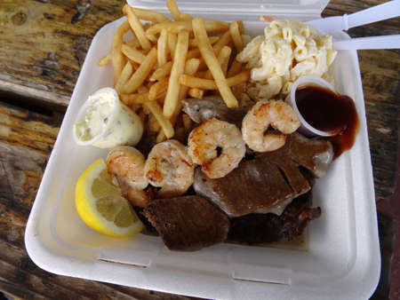 ahi: Mix Plate Dish of Shrimp, Grilled Ahi, Steak, french fries, macaroni salad, lemon slice, small cups of steak and tartar sauce in a plate with plastic knife and fork on a wooden table. Stock Photo