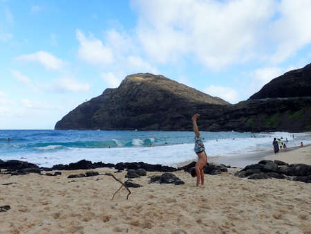 beach hunk: Man Handstanding on Makapuu beach as wave crash on the South east Shore of Oahu, Hawaii.