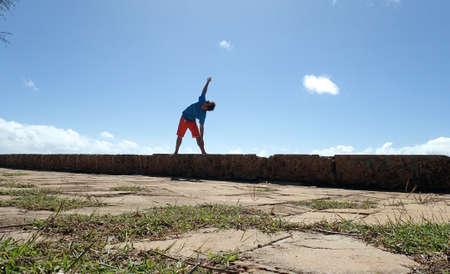 man enjoying yoga outdoors doing the pose Triangle Pose, Trikonasana,  on rock wall by ocean on Oahu, Hawaii. Фото со стока