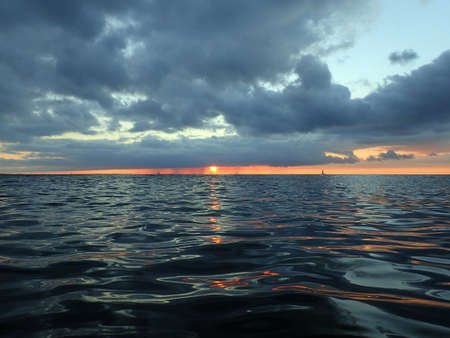 lowers: Sun dips below clouds as it lowers to the Pacific ocean with boats on the horizon of the water light reflecting of Oahu, Hawaii.  December 2015. Stock Photo