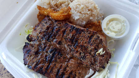 BBQ and Seafood Combo featuring New York Steak, Fried Shrimp, Rice, cabbage, and tarter sauce in a styrofoam plate. Stock Photo