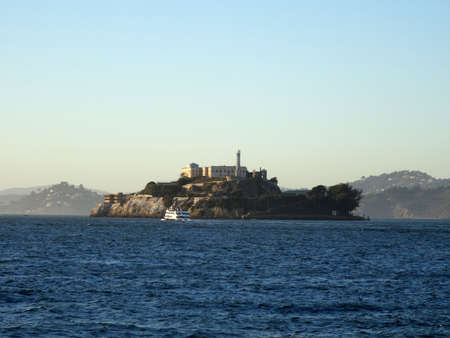 san francisco bay: Alcatraz Island with Lighthouse and Prison in view and boat passing by on a nice Day in San Francisco Bay. Stock Photo