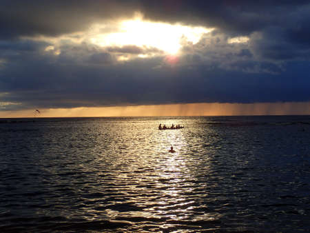 oahu: Sunset through the clouds and reflecting on the Pacific ocean with people playing and canoeing in the water of Oahu, Hawaii.  December 2015.