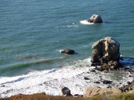 marin: Waves roll toward large rocks and shore on the coast of Marin in California. Stock Photo