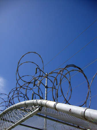 chainlink fence: Barb Wire Covers top of Fence covering with Power lines above and blue sky.