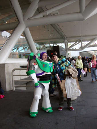 buzz: SAN FRANCISCO, CA - APRIL 4: Man dressed as Buzz Lightyear characters poses for photo with man holding bags and wearing hat outside the Wondercon convention. April 4, 2010 at Moscone convention center in San Francisco.