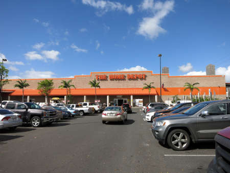 car retailer: Honolulu, HI, USA - August 4, 2015: Oahu Home Depot parking lot filled with cars.  Founded in 1978, The Home Depot is a retailer of home improvement and construction products and services. It is the largest home improvement retailer in the USA.
