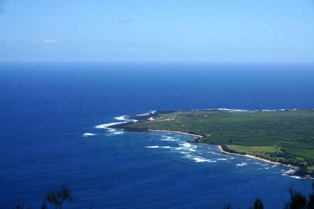 Waves roll towards Kalaupapa Peninsula with airport and Lighthouse in view on Molokai, which is the site of Saint Damiens mission where he ministered for 16 years to those suffering from Hansen disease.  Seen from lookout.