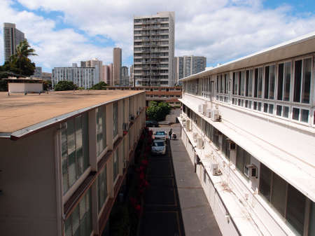 highrises: Alley between buildings with cars and Homeless person with shopping cart.  Highrises and surrounding Honolulu cityscape visible. Stock Photo