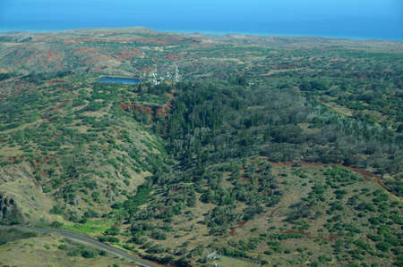 largely: Aerial of countryside running to the ocean with Water reservoir and communications towers on Molokai with roads, largely undeveloped with trees and bushes. April 2016.