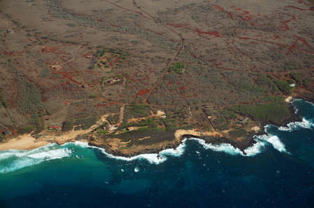 largely: Aerial of Northwest coast beach of Molokai with waves crashing into shore and surrounding area of island with roads, homes, but largely undeveloped. April 2016. Stock Photo