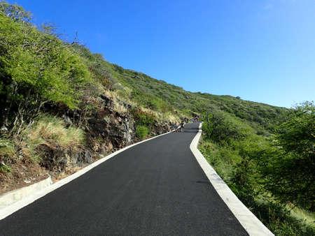 empedrado: Camino pavimentado que conduce al sendero Makapu'u Point rodeado de exuberante vegetación verde en Oahu, Hawaii. 27 de diciembre de 2015.