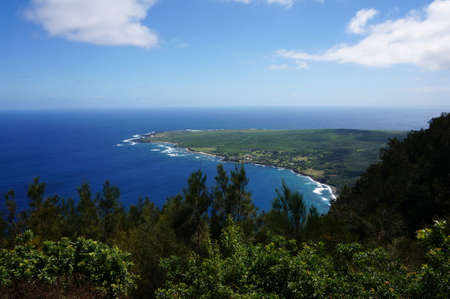 Waves roll towards Kalaupapa Peninsula on Molokai, which is the site of Saint Damiens mission where he ministered for 16 years to those suffering from Hansen disease.  Seen from lookout. Stock Photo