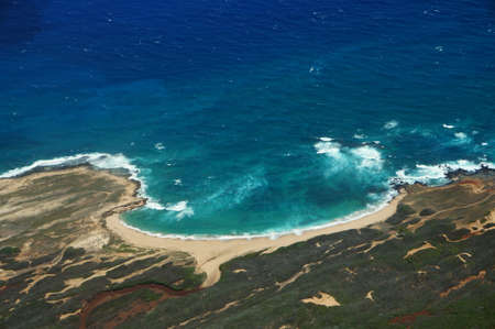 largely: Aerial of coastline of Molokai with waves crashing into Moomomi beach, rocky shore and surrounding area of island with dirt roads, largely undeveloped. April 2016.