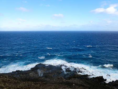 orificio nasal: rociadores de agua de cada orificio nasal en la orilla roca de lava con el océano en el horizonte en el punto de Makapuu en Oahu, Hawaii. 2016. Foto de archivo