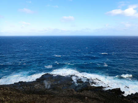 orificio nasal: Water sprays out of blowhole on lava rock shore with ocean on the horizon at Makapuu point on Oahu, Hawaii. 2016.