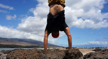 Man Handstands on Lava rocks of Molokai Harbor in the state of Hawaii. Stock Photo