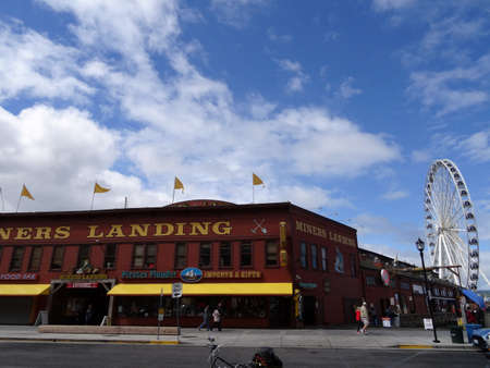 elliot: SEATTLE-- JUNE 24: Miners Landing at Pier 57 with signs of tourist businesses and of Great Ferris Wheel on June 24, 2016 in Seattle, WA. Seattles waterfront is a very popular tourist destination. Editorial