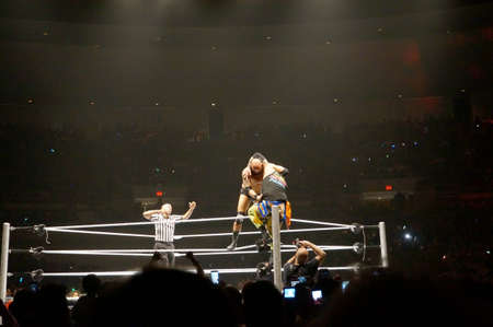 wrestlers: HONOLULU - JUNE 29, 2016: WWE wrestlers Karl Anderson setup a superplex to Uso on top rope of ring during match at WWE event at the Neal S. Blaisdell Center, Honolulu on June 29, 2016 Honolulu, Hawaii.