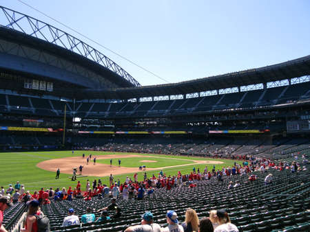 SEATTLE - JUNE 26: Crew cleans field and people fill into seats at Safeco Field before baseball game, Seattle in June 26, 2016. 新聞圖片