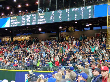 outfield: SEATTLE - JUNE 24: fans in bleachers do the wave with scoreboard above at Safeco Field during baseball game, Seattle in June 24, 2016. Editorial