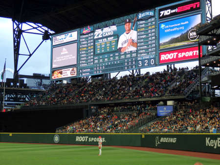 outfield: SEATTLE - JUNE 24: Cardinals Stephen Piscotty Player stands in the outfield with fans in bleachers and Robinson Cano on the scoreboard at Safeco Field during baseball game, Seattle in June 24, 2016. Editorial
