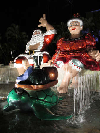 HONOLULU - DECEMBER 14: Mr. and Mrs. Claus sit on top waterfall with Turtle figure holding tray with coconut drink, poi bag, and Lau lau Light up at night in front of Honolulu Hale, the Mayor Office, as part of Honolulu City Lights runs annually throughou