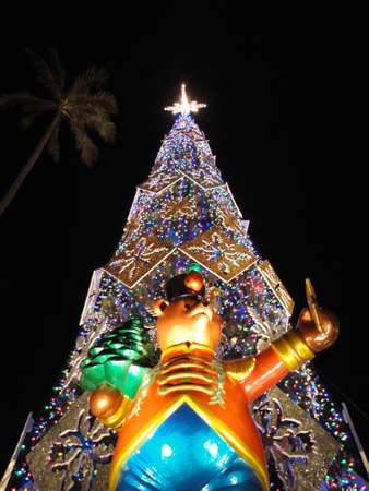 HONOLULU - DECEMBER 5: Bear figure in suit holding a tree stands in front of a lite up at night 50-foot Norfolk pine Christmas Tree in front of Honolulu Hale, the Mayor Office, as part of Honolulu City Lights runs annually throughout the month of December Editorial