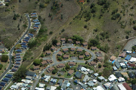 Aerial of luxury residential town with House, many of which feature roof top solar, on slopes of Mountain on Oahu, Hawaii.
