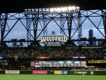 outfield: SEATTLE - JUNE 24: Cardinals Players stands in the outfield with fans in bleachers and Nick Vincent on the scoreboard at Safeco Field during baseball game, Seattle in June 24, 2016.