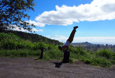 Man wearing beanie, muscle t-shirt, yoga pants, and slippers does balances on hands as he does Mayurasana or Peacock Pose on tree stump on Tantalus mountain of Oahu with Honolulu cityscape in the distance on a beautiful day. Stock Photo
