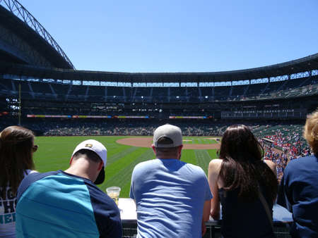 outfield: SEATTLE - JUNE 26: People lean on rail and look at field at Safeco Field before baseball game, Seattle in June 26, 2016.