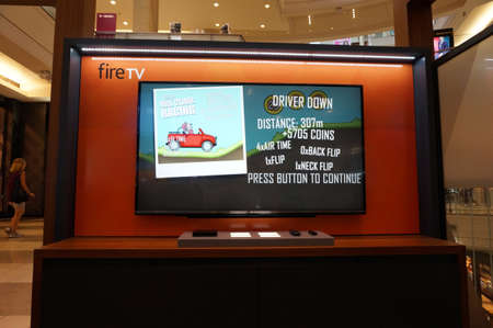 amazon com: SAN FRANCISCO - OCTOBER 11:  Amazon Fire TV with Hill Climb Racing playing on display on  wall in San Francisco mall in California on October 11, 2015.  Amazon is an American international electronic commerce company. It is the worlds largest online reta