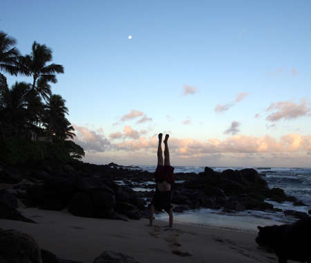 beach hunk: Man Handstanding on beach at dawn as wave crash on the North Shore and moon in the sky of Oahu, Hawaii.
