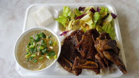 Kalbi Combo with Chicken Long Rice Plate with salad and coconut pudding on a white table