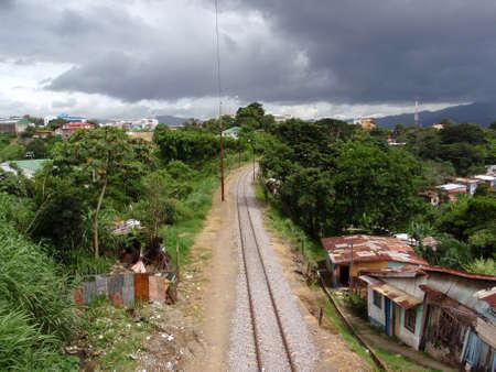 SAN JOSE, COSTA RICA - JULY 13: Train tracks run into the distance though neighborhood on a cloudy day, taken July 13, 2009, Downtown San Jose, Costa Rica. Stock Photo