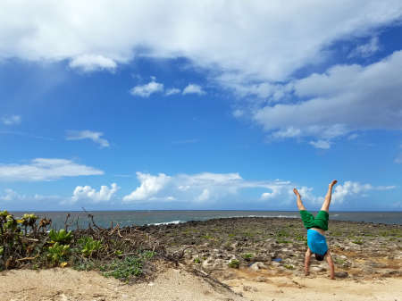 beach hunk: Man Handstanding on beach as wave crash and clouds in the sky on the North Shore of Oahu, Hawaii.