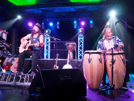 HONOLULU, HI - FEBRUARI 22: Musicus Tavana speelt gitaar en zingt met Leon Mobley drummen op het podium bij Crossroads in Hawaiian Brian's met gave verlichting op 22 februari 2017, Honolulu, Hawaii. Redactioneel