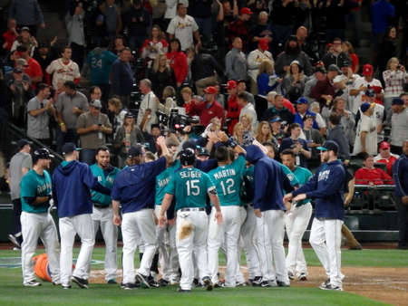 outfield: SEATTLE - JUNE 24: Players of home team Mariners celebrating winning game at home plate at Safeco Field baseball game, Seattle in June 24, 2016.